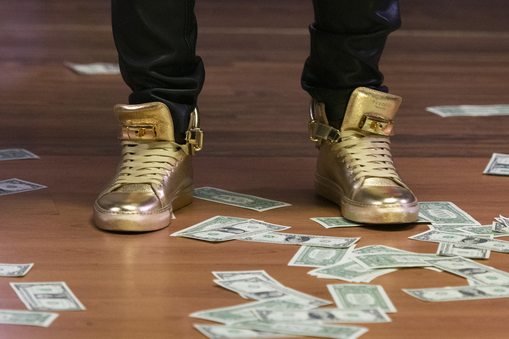 Money lines the stage beneath gold painted shoes as Yinka Rythmz performs during the I Am Somebody Las Vegas 2.0 show at Mia's Banquet Hall in Las Vegas, Saturday, Dec. 17, 2016.