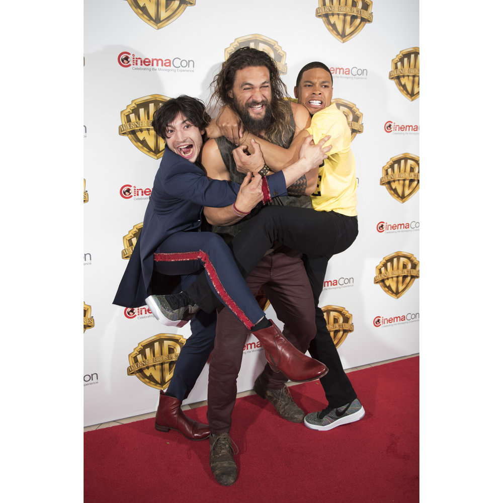 Jason Momoa, center, Ezra Miller, left, and Ray Fisher of the movie Justice League arrive to the Warner Bros. red carpet during CinemaCon at Caesars Palace in Las Vegas, Nev., on March 29, 2017.