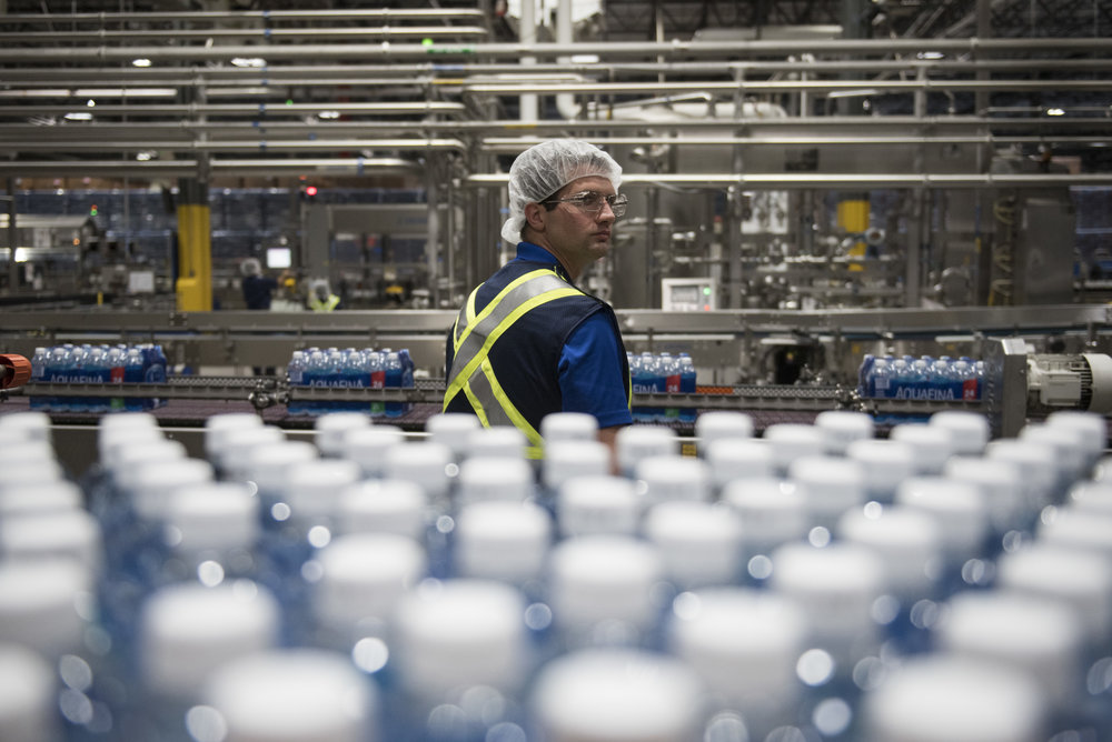 A PepsiCo employee monitors packages of Aquafina water on the production line at the PepsiCo factory in Las Vegas, Nev., June 19, 2017.