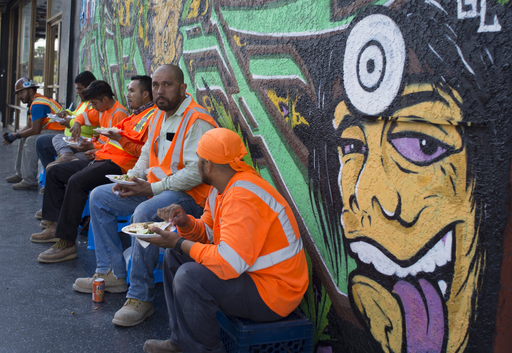 Construction workers take a lunch break on Hollywood Boulevard at El Centro Avenue in Los Angeles, Calif., Sept. 6, 2017.