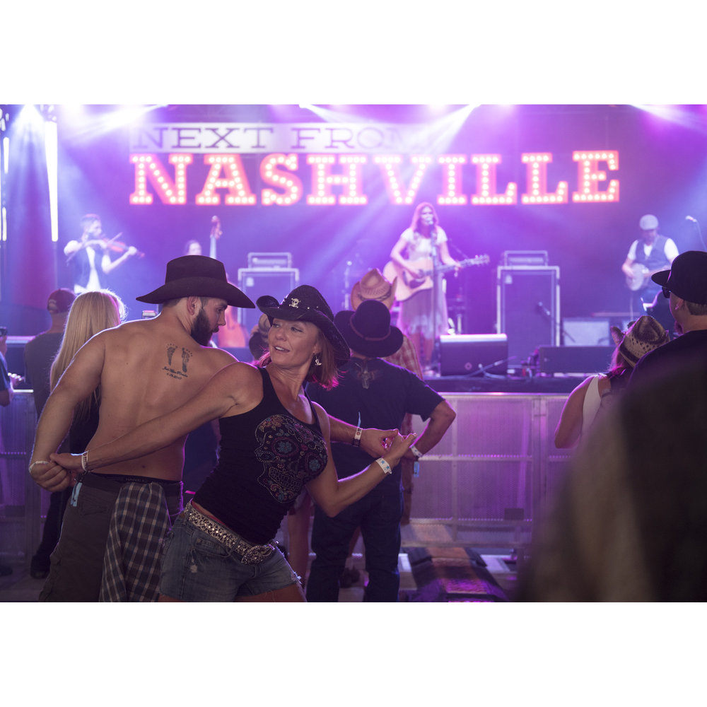 Members of the audience dance during Ruthie Collins' performance at the Next from Nashville stage at Route 91 Harvest Country Music Festival at MGM Resorts Village in Las Vegas Friday, Oct. 2, 2015.
