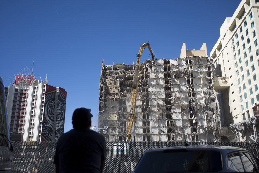 A man watches the demolition of Las Vegas Club from Fremont Street Experience in downtown Las Vegas, Nev., Oct. 14, 2017.