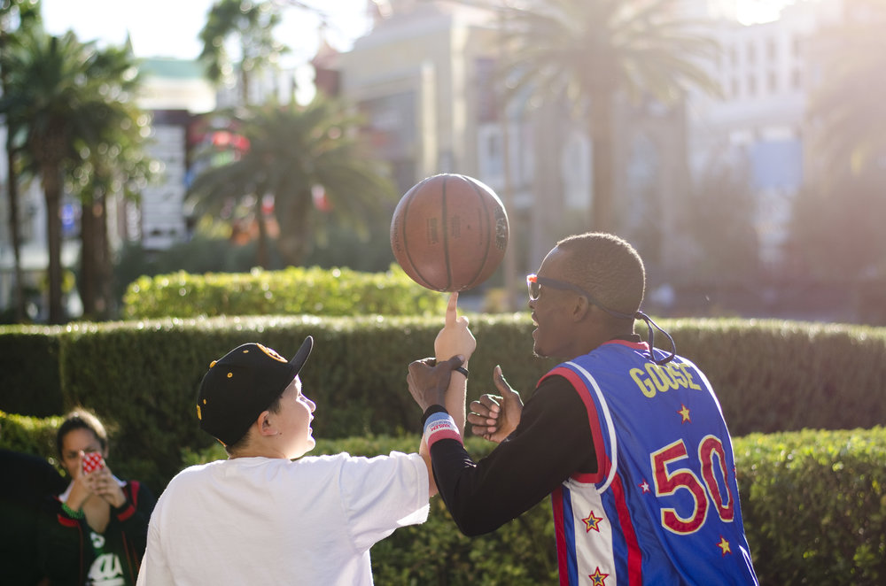 "A busker dressed as Reece ""Goose"" Tatum of the Harlem Globetrotters teaches a kid how to spin a basketball on his finger on the Strip near Tropicana Avenue in Las Vegas."