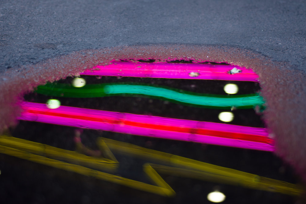 Neon is reflected in a puddle at New York New York hotel-casino in Las Vegas, May 10, 2018.