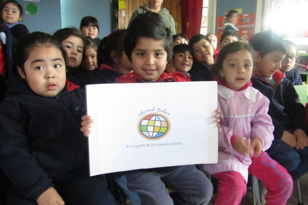 A school child in the Araucania region of Chile holds the Choral Tales logo