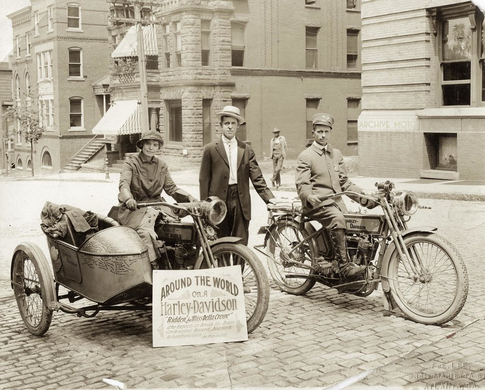 Here is the lovely and rugged Miss Della Crewe on the streets of Atlanta in September, 1915 after having just returned to the US from her continued motorcycling adventures in South American and the Caribbean. She sits atop her 1914 Harley-Davidson sidehack rig adorned with the names of towns and states which she had visited the year before, as well as the plates, plaques, and badges from her recent international trips. After beginning her journey in June the year before, Crewe had traveled over multiple continents, numerous countries, countless states, and had covered nearly 11,000 miles with only the company of her trusty companion Trouble, a feisty little terrier, who is somewhere out of frame assuredly living up to his name. She is accompanied by local Harley-Davidson dealer Gus Castle and an Atlanta Police Officer.