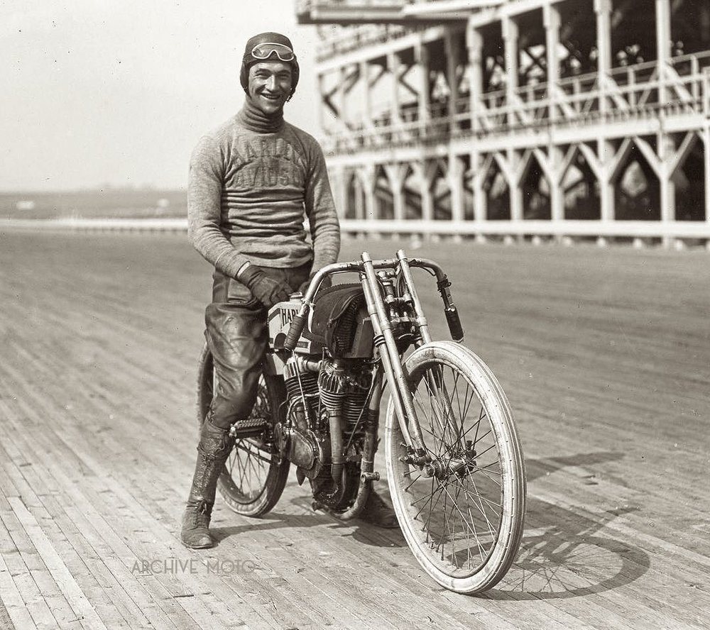 "Photographed here is Harry ""Otto"" Walker onboard a new factory works Harley-Davidson 11K series machine on the poplar boards at Speedway Park. The image comes from the F.A.M. American Championship 300 Mile race held September 12, 1915.  The scale and refinement of the Maywood track is evident in the background, it truly was a venue unlike any other before. Walker, who had recently won the big race in Venice as well as the 2nd annual Dodge City 300 set a new record for 100 miles with an average speed of just a hair under 90 mph, but his machine chewed up a valve on the 188th lap and was unable to finish. Out of the 27 riders entered Carl Goudy, onboard a big-valve Excelsior took home the $1,000 first prize, Indian's Teddy Carrol came in second, and Walker's Harley-Davidson teammates Ray Weishaar and Bill Brier placed fourth and fifth."