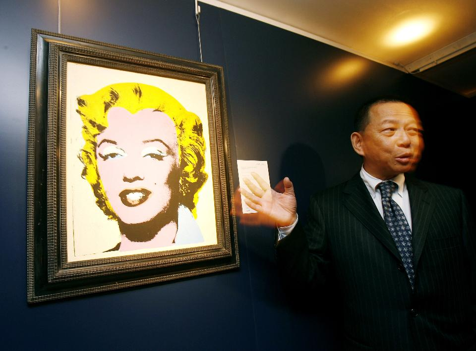 "Ken Yeh, deputy chairman of Christie's Asia gestures in front of a painting by Andy Warhol entitled ""Lemon Marilyn""during an auction preview in Hong Kong, 2007. AP Photo/Vincent Yu Image courtesy of Forbes"