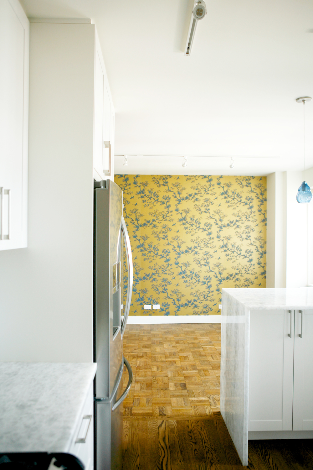 Love the contrast of the white kitchen and the gold wallpaper.