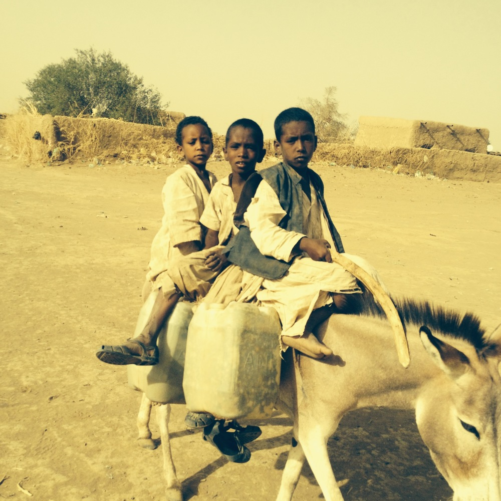Children delivering water to families around the village