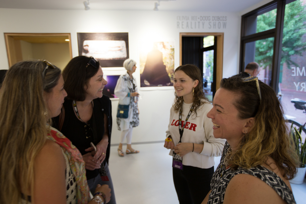 Festival attendees conversing with Olivia Bee in her exhibition space during the Toast the Artist Gallery Walk.