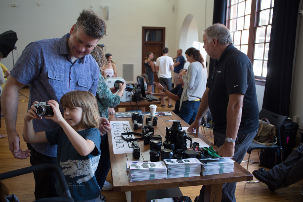 Community members visit Fujiphoto USA's table during Family Photo Day at the Jefferson School African American Heritage Center   Photo © Jon Golden