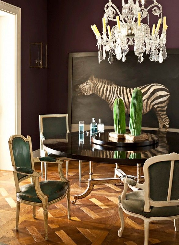 The sophisticated nature of this space calls to me. The eclectic frames of the chairs, all upholstered in different shades of emerald and greens. Love the dark table and the artwork.