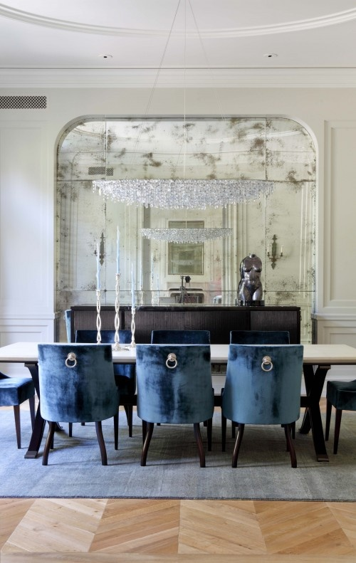 The shiny pulls on the back of these chairs complement the shiny nature of the antiqued mirror wall.