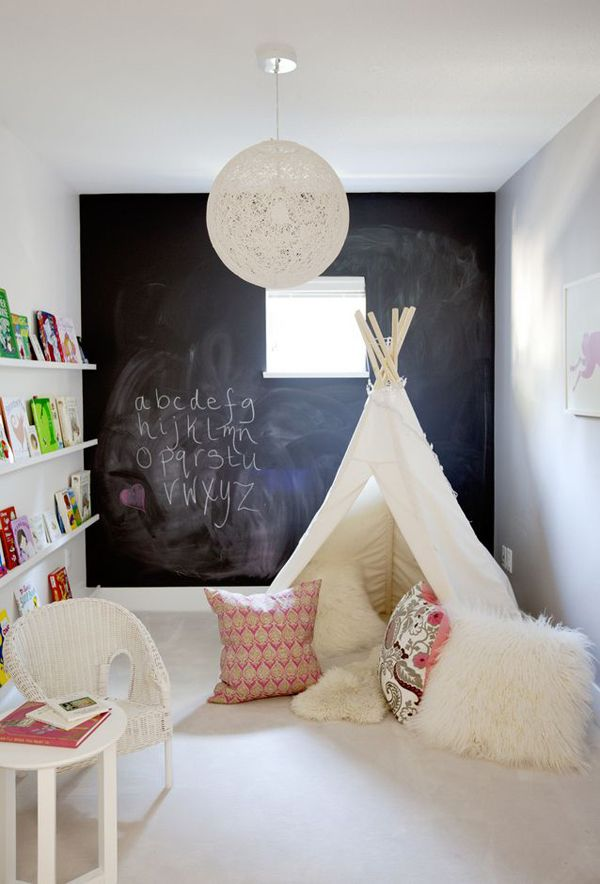 This room uses an overall neutral color palette and lets the children's toys and books bring in pops of color. Love the idea of using a collection of toys or books to create art on the walls. The chalk wall has become a classic feature in children's spaces.