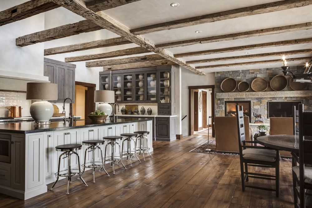 Squaring off the cabinetry and keeping it simple and understated contrasts the rustic nature of the wooden beams and flooring. A collection of White Pottery in the kitchen hutch keeps the space clean and modern.