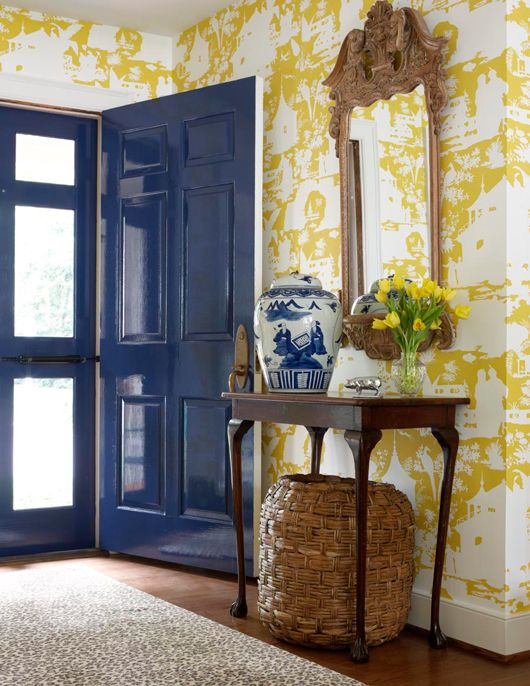 Citrine wallpapered entry. Striking contrast with the glossy blue painted door.