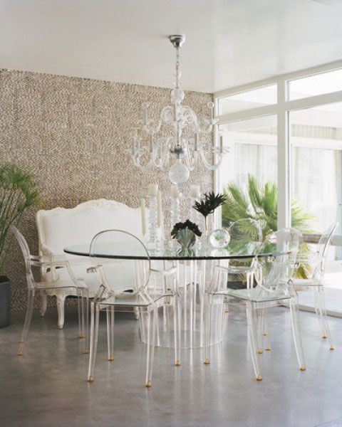 A traditional banquette, modern glass table, and lucite ghost chairs. With so many layers, the lucite chairs bring translucent function.