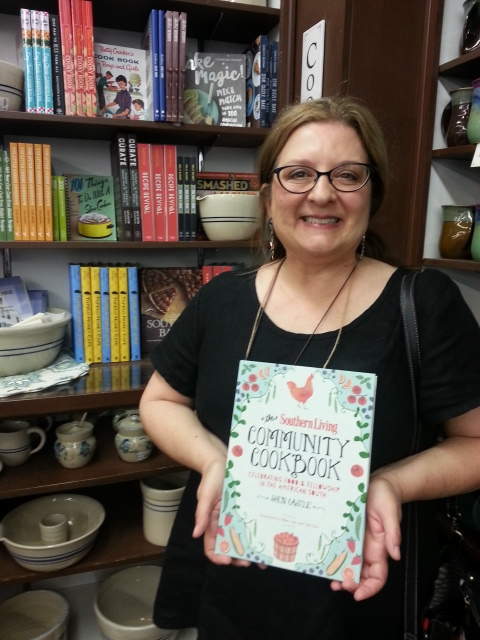 "Sheri Castle holding a copy of her cookbook ""The Southern Living Community Cookbook, Celebrating Food and Fellowship in the American South""."