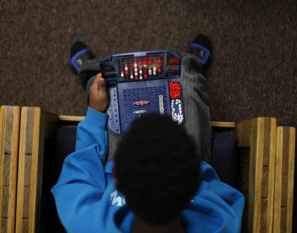 A boy spends his afternoon at the Bridge playing games with staff. The number of teens in Grand Rapids who do not know where they will sleep is estimated at 200.