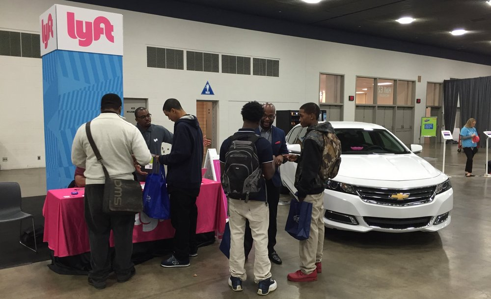 Lyft team members talk with attendees at Detroit's Pathways to Success job fair about how Lyft might fit into their future.