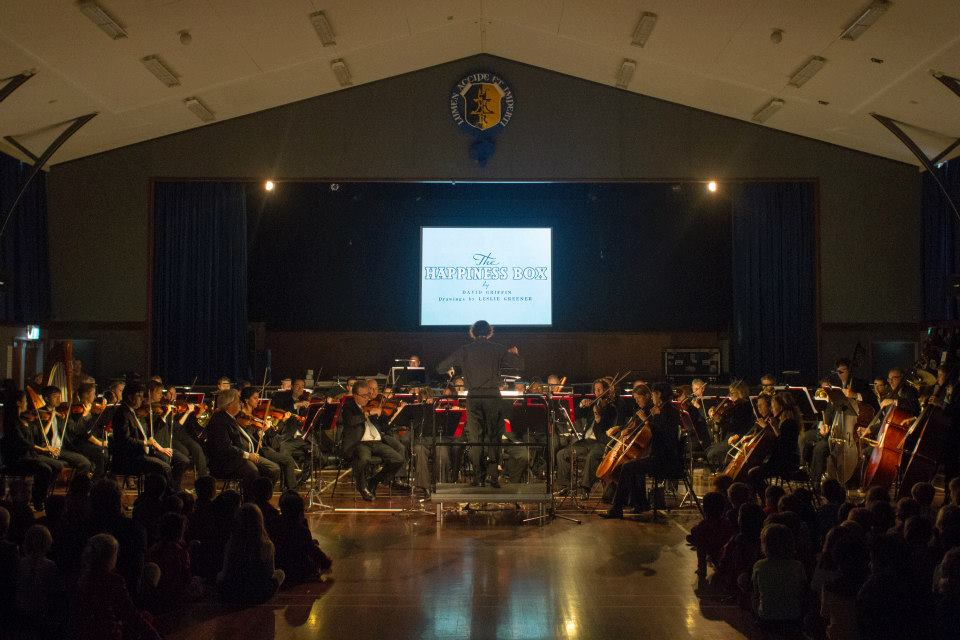 Conductor Hamish McKeich, leading the NZSO in a performance of 'The Happiness Box' at Rongotai College, Wellington, 13 May 2015