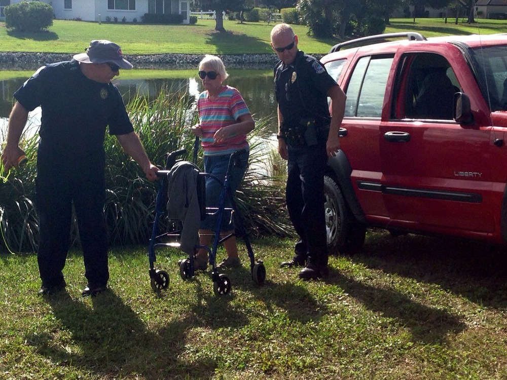 Sgt. Jim DeNiro and Officer Thomas Wagonseller helping one of the passengers, Darlene Miller, remove her items from the vehicle.