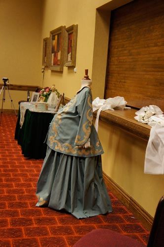 The Victorian decorations includes gloves, hat boxes, a baby carriage, dolls and even this maternity gown.