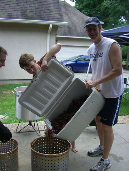 Greg teaching the boys the ropes. Our nephew is on the left side of the pic. He's wearing mitts so he can scoop the live crawfish into the cook pot. Our oldest son (in the middle) is helping Greg with the cooler. That thing is heavy with all those crawdads in it!