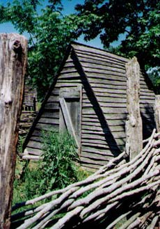 This is the hen house enclosed by a twilled, wooden fence comprised of thin rails passing over and under sturdy posts.