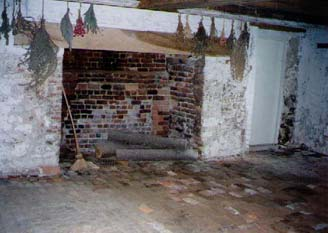 This is the actual basement/kitchen with brick walls and brick flooring, as well as the fireplace where all the cooking for the family would have been done.