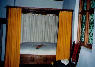 Another view of the bed, the bed curtains and the bed key. The window is a reproduction of the diamond-paned ones originally in the house.