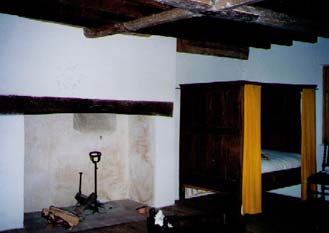 Here is a view of the master chamber's fireplace. I can't find in my notes what they call that thing in the fireplace (maybe somebody can email me), but it was used to warm up your brandy. You'd set the bottle in it until it reached the temperature you wanted. Do you see the beams on the ceiling? Those support the flooring one level up. Therefore, you could hear through the floors and even look down through the cracks!
