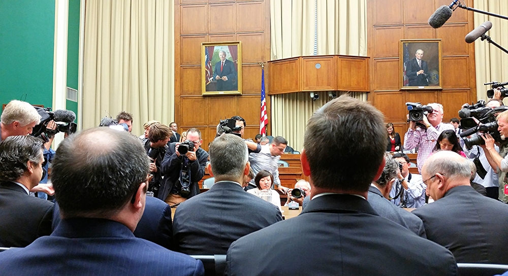 Volkswagen's U.S. chief Michael Horn (center left, gray hair), faces cameras before a House hearing on the company's emissions cheating
