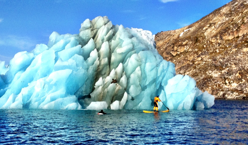 Mike Libecki stand up paddle boarding by an iceberg.