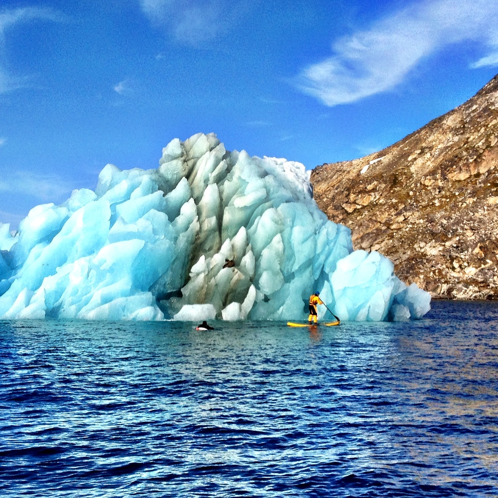 Mike Libecki stand up paddleboarding in front on an iceberg in Greenland