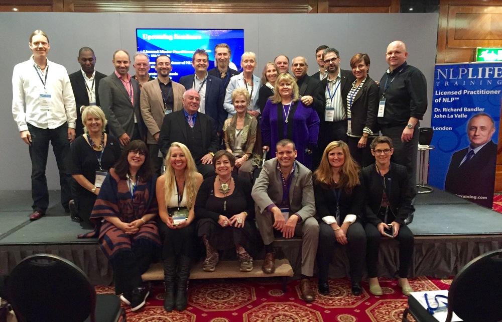 Dr. Richard Bandler ja hänen avustavien kouluttajien tiiminsä Lontoossa 10/2015. Petri on ylärivissä vasemalta seitsemäs ja ryhmän keskellä istuu Dr. Bandler yhdessä vaimonsa Glendan kanssa.