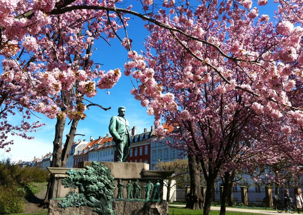 Kongens Have en solskinsdag i april med blomstrende træer og Viggo Hørup, der skuer ud over folk, der slikker solskin i sig, børn i klapvogne, hundeluftere, turister - og alle os andre. Hvadmon hantænker?