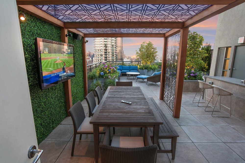 manhattan roof garden terrace design with pergola and outdoor tv