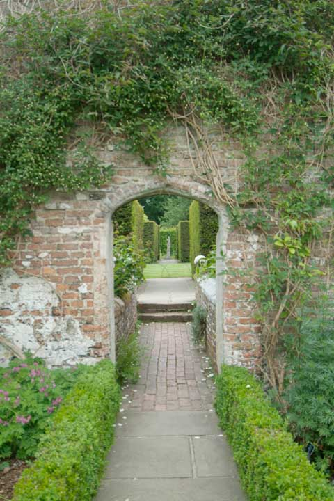 A country estate garden, old brick walls with vines