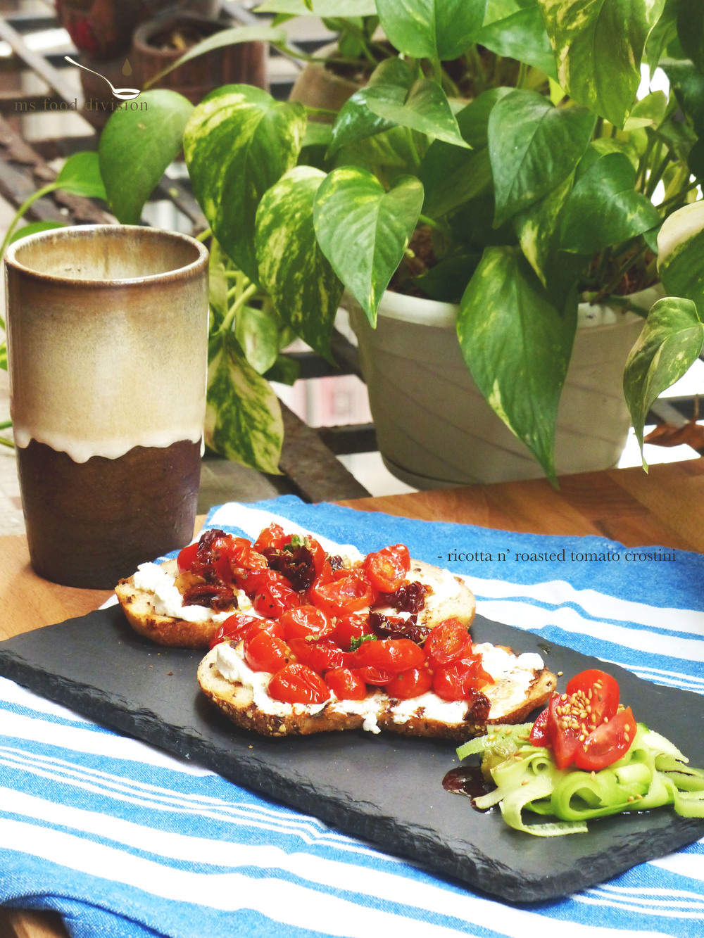 Ingredients: (for 2 servings)   2 slices grilled/baked thin baguette *  100g cherry tomatoes, halved  2-3 tbsp ricotta  1-2 tbsp honey  2 pieces sun-dried tomatoes, thinly sliced  1 garlic, finely chopped  extra-virgin olive oil  1 tsp dried oregano   Instructions:    1) Preheat oven at 180ºC    2) Place the halved cherry tomatoes with oil, season, bake for 10-15 minutes    3) Preheat a stir fry pan with olive oil, add garlic and sun dried tomato under medium low heat; stir and let cook for 3-5 minutes until the sun-dried tomatoes look a little crispy. Turn off the fire.     4) Transfer the sun-dried tomatoes to the baking dish of cherry tomatoes and bake for around 5 minutes.     5) Spread the ricotta cheese generously on the grilled baguette surface. Add honey on the cheese.     6) Top with the roasted tomatoes and oregano. And ready to serve! :)    * I usually like to use a griddle pan to toast my baguettes (I love those little burnt lines on my bread) but feel free to use an oven if you desire.