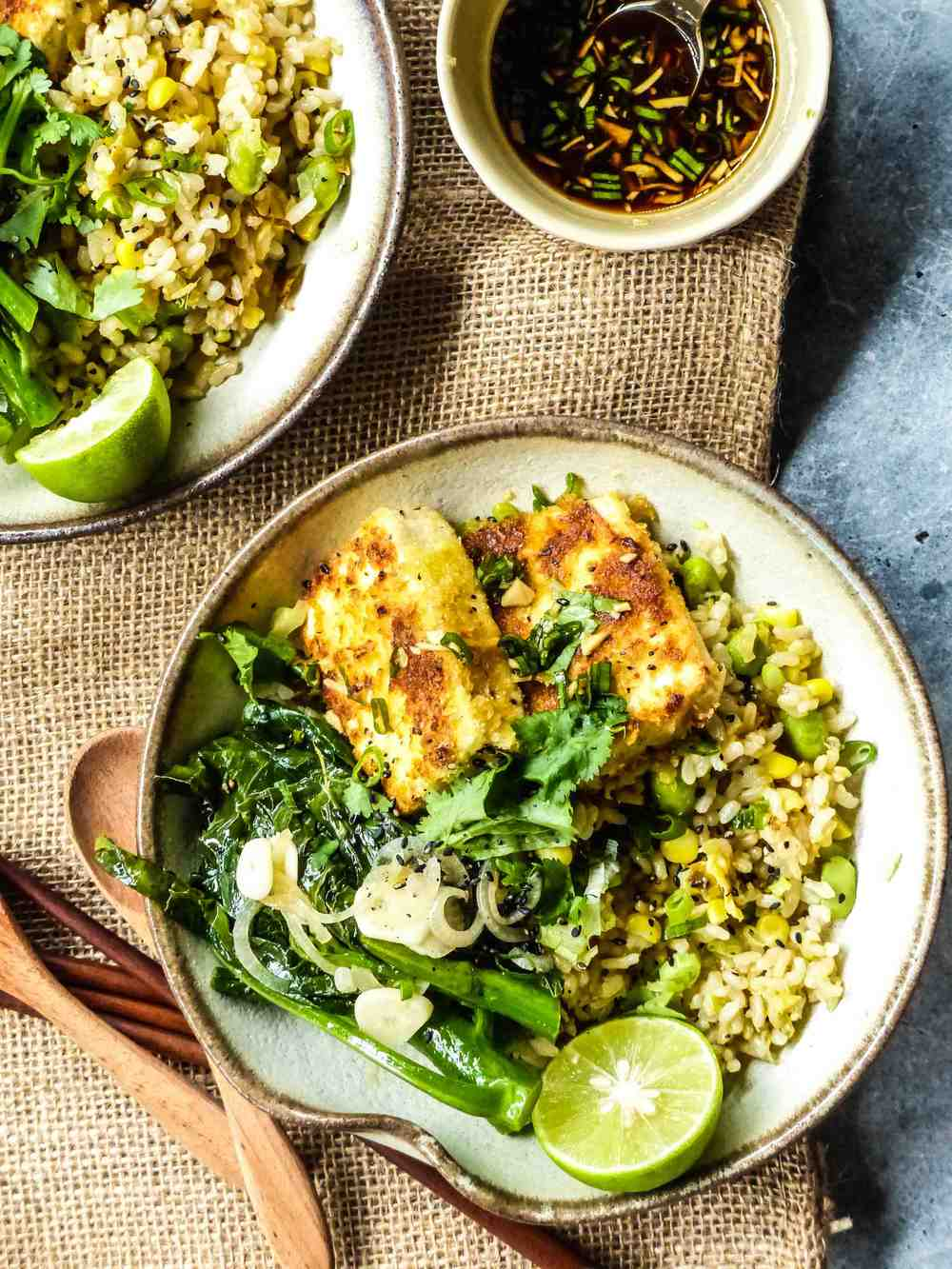 Servings: 2 persons    Preparation Time: 5-10 minutes    Cooking Time: 15-20 minutes    Ingredients:      For fried rice:            2 bowls cooked brown rice  1/2 bowl cooked corn  1/2 bowl edamame  1/2 onion, finely chopped  2 tbsp minced ginger  1-2 tbsp chopped spring onion and coriander  extra-virgin olive oil    For Chinese Kale:     100-150g Chinese Kale  1/2 vegetarian stock tablet  1 shallot  1-2 garlic cloves  extra-virgin olive oil    For crispy tofu:     150g hard tofu, squared  1 egg*   1/2 cup breadcrumbs  1 garlic clove, finely chopped  1/2 green chili, finely chopped  1/2 red chilli, finely chopped  * some leftover egg can be used for making the fried rice    For the sweet and spicy lime sauce:    1/2 lime juice  1-2 tsp honey  1-2 tsp mirin  2 tbsp soy sauce  1-2 tbsp chopped spring onion  1/2 garlic clove, finely chopped  1/2 red chili, finely chopped  1/2 green chili, finely chopped