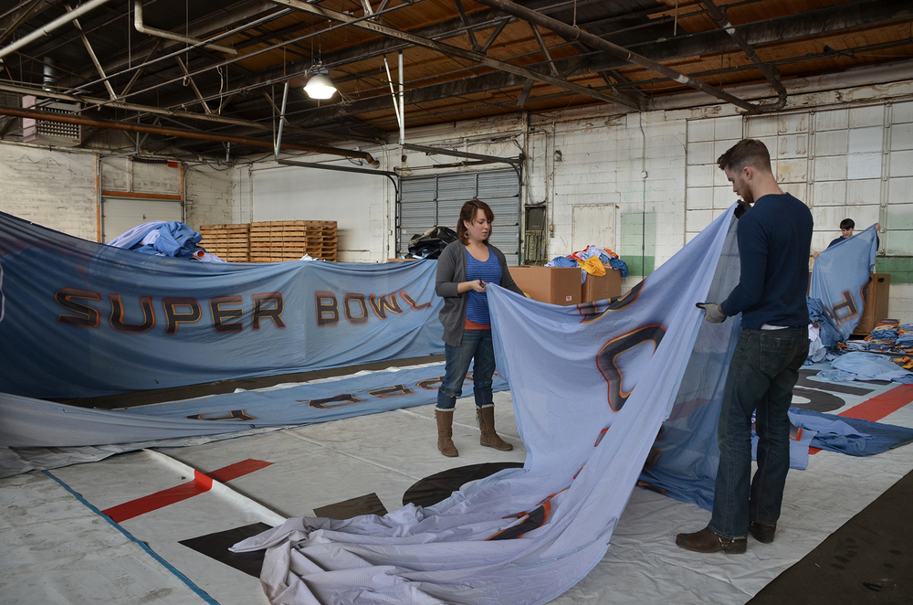 Super Bowl XVLI fabric being cut and processed by some PUP volunteers (The very talented Ray & Nick).