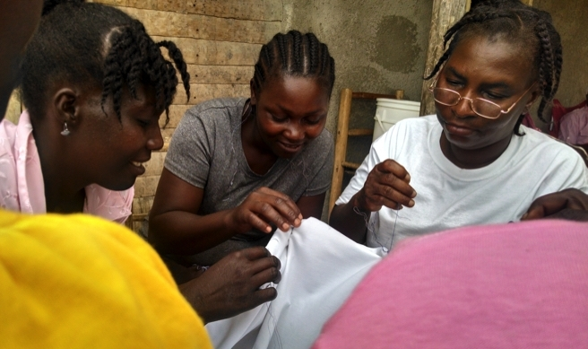 Women who work with Nou Hope hand-embroider cloth in Haiti.