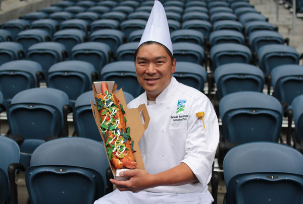 Portrait of CenturyLink Field Executive Chef Seis Kamimura with the new 24-inch-long Colossal Hawk Dog for Seahawks games.