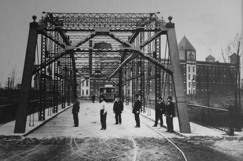 The iconic iron bridge was constructed in 1894, allowing the trolley to cross the Elkhart River. In the background you can see the Old Bag Factory, operating as the Cosmo Buttermilk Soap Co. at the time. Photo via the Goshen News.