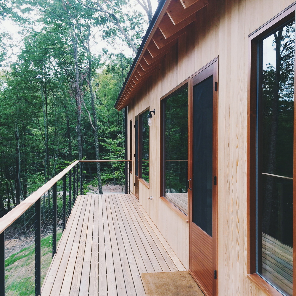 the deck, which wraps around the first (upper) level of the cabin.