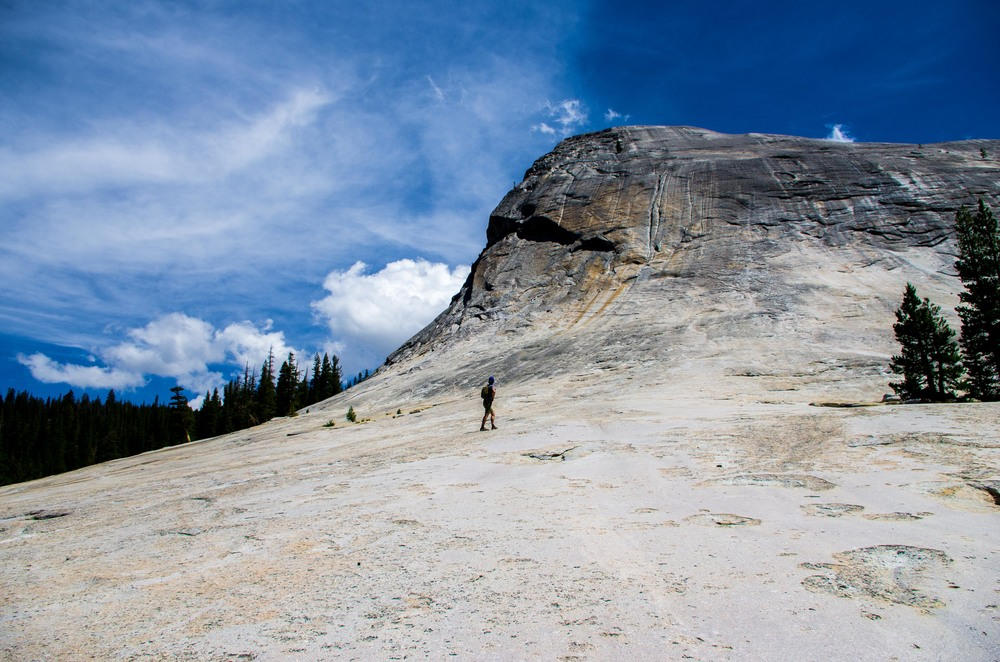 Walking up the the start of the Class III southeast face of Lembert Dome in Tuolumne Meadows. Yosemite National Park, California