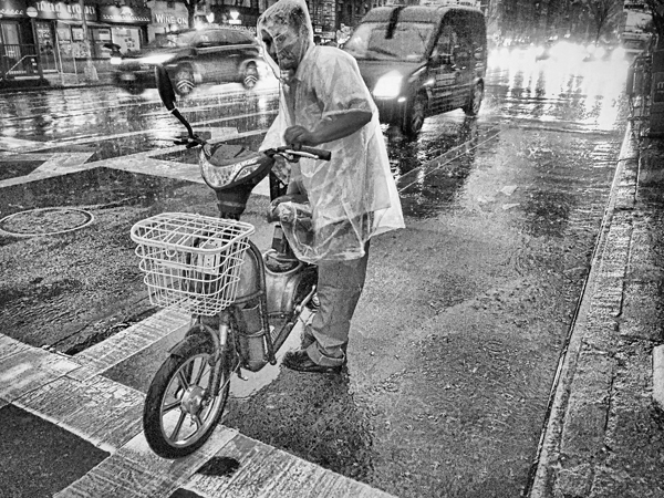 Man and His Scooter In The Rain