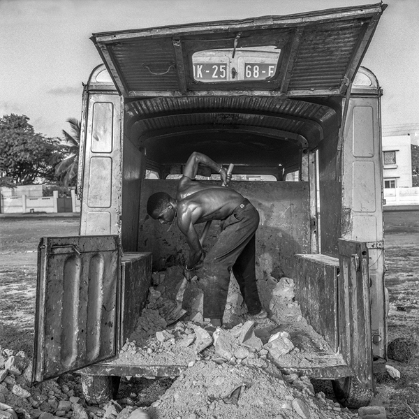 Man Shoveling in the back of a Truck